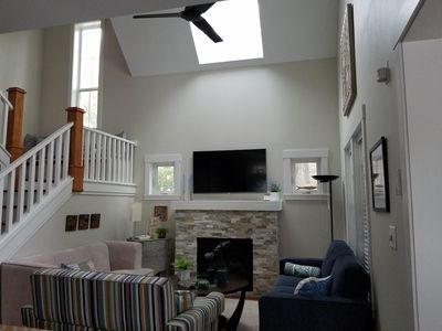 Bright living room with gas fireplace, ceiling fan, vaulted ceiling and skylight
