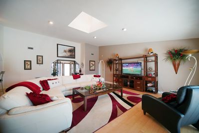 """The living room with large leather sectional and 55"""" television."""