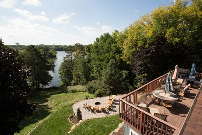 The spacious deck, the cozy fire pit, and the peaceful lake under a blue sky!