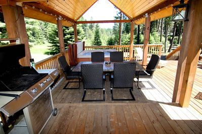 Large, spacious deck with grill, patio seating and a covered hot tub.