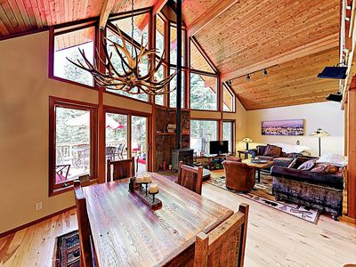 Living & Dining Areas - The spacious living area features vaulted open-beam ceilings, hardwood flooring throughout, and a classic wood-burning fireplace stove.