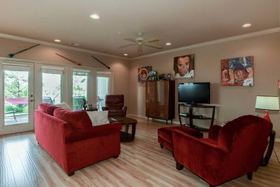 Living room includes large flat screen television and plenty of comfortable seating options - not to mention beautiful one-of-a-kind art!