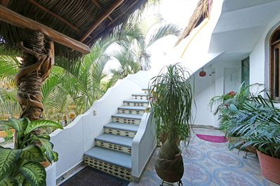 Your curved outdoor staircase to double wooden doors on balcony to Villa