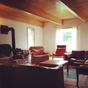 Large living room with wood stove, comfy chairs and bright light.