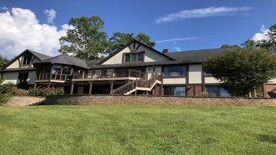 Back of lake house with huge deck and and sitting area underneath.