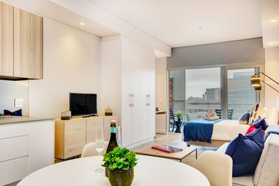 Spacious living are with dining table, TV, bed and balcony