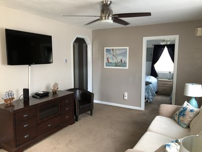 Living room with large screen cable TV, ceiling fan.