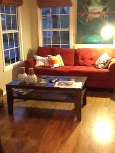 Bright and sunny living room. Comfortably furnished. Large Flat Screen TV.