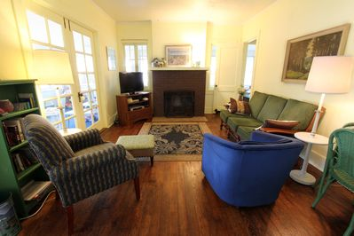 The comfy living room is the hub of activity with French doors showing the porch