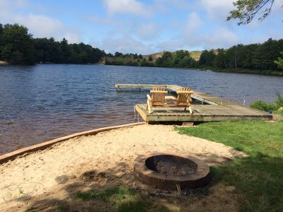 A view from the back of the cabin of the lake, dock, and fire pit.