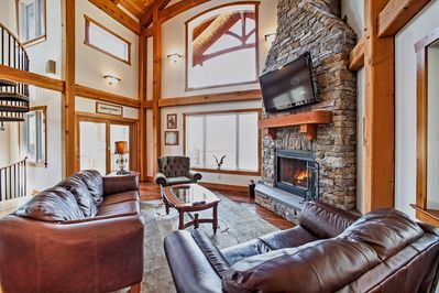 Soaring ceilings and a stunning stone fireplace adorn the cozy living room.