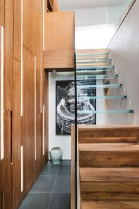 Beautiful architect-designed glass and walnut staircase joining the two levels
