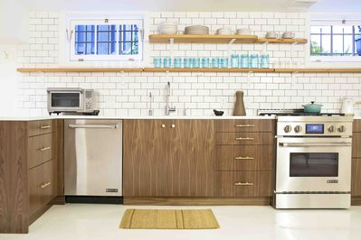 Kitchen with Walnut cabinets , commercial range, and beautiful tile.