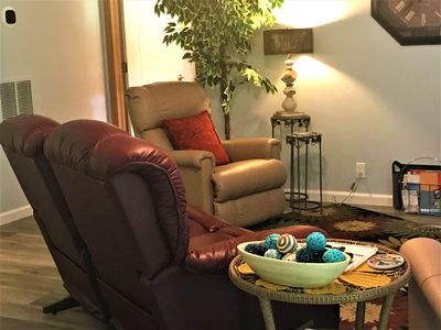 cozy living room with a double recliner loveseat and two single recliners.
