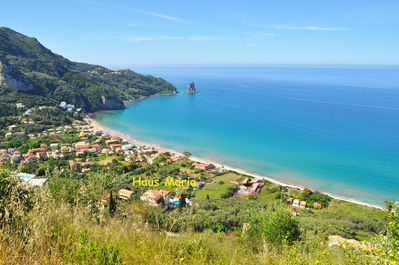 """The bay of Agios Gordios, with its gently sloping beach and the House """"Maria""""."""