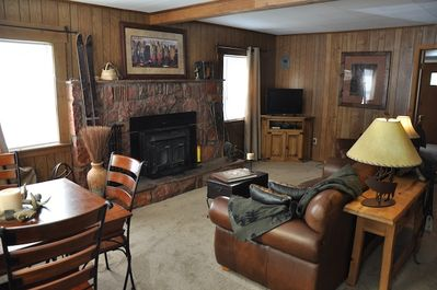 Living room with wood burning fireplace and dining table