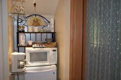 Mini kitchen with fridge, microwave, coffee maker, kettle, coffee, hot chocolate, tea, bottled water, etc.