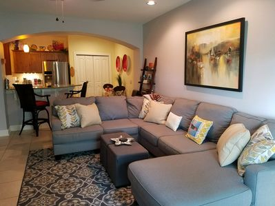 Spacious living room with wrap around coziness and open to kitchen area