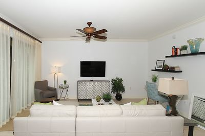 """Come and relax in this spacious family room with a 55"""" TV and leather sofa."""