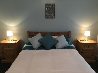 Spacious bedroom with double bed, bedside cabinets,  wardrobe at Pebble Cottage