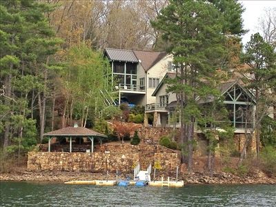 view of home from water showing main dock and stone patio with covered gezebo