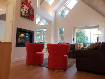 living room has vaulted cedar plank ceilings and opens to a covered balcony