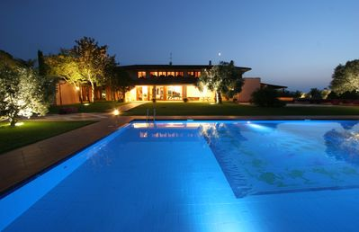Front view of the villa and pool at night.