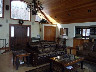 Main level entry to Great Room with chandelier & wood paneled ceilings.