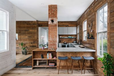 Kitchen viewed from living area highlighting brick chimney and reclaimed wood