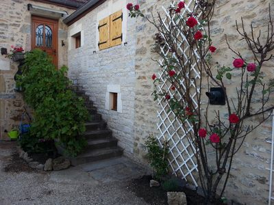 Fragrant roses and grapevine greet you inside the stone-walled & gated courtyard