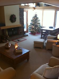 Open family/ dining area with wood fireplace, opens out to deck and gas grill.