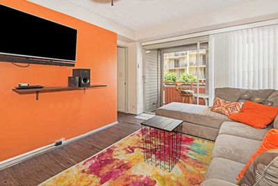 Tan sectional couch facing an orange wall with a mounted flat screen TV