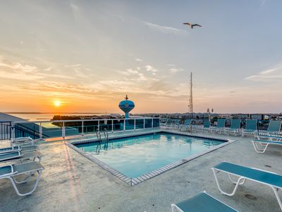 Photo for Bayfront condo w/ updated decor, balcony & shared pool - walk to beach!