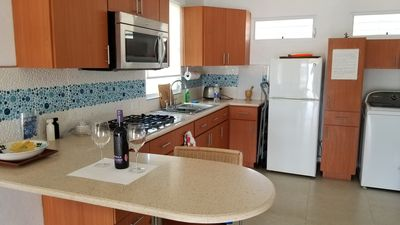 The Kitchen is bright and breezy with a gas stove and Italian barstools.