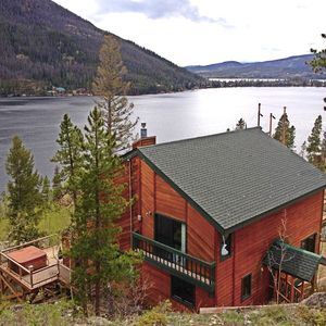Tri-level mountainside home overlooking lake with hot tub.