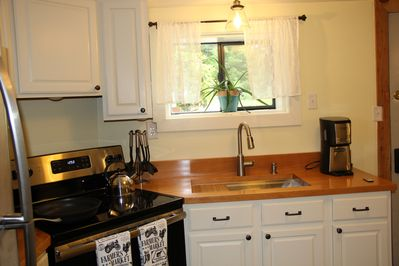 New Kitchen with custom wooden countertops & stainless steel appliances
