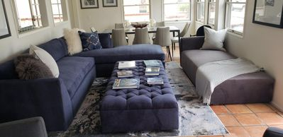 Large sofa with sleeper bed, chaise lounge that sleeps one and dining table.