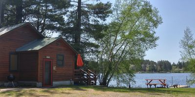 Side view of main cabin and dock. Level frontage, close to water w/lakeside deck