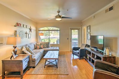 Relax on the comfortable couch in the living room while watching your favorite show on the flat screen cable TV.