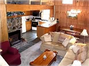 The living/dining/kitchen area. Open beam ceilings & a native stone fireplace.