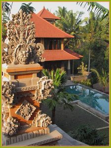 The hand-carved Balinese temple with the house and pool in the background