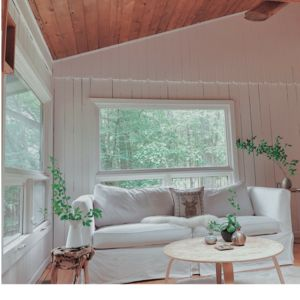 The bright living room with wood burning fireplace, mountain + forest views.