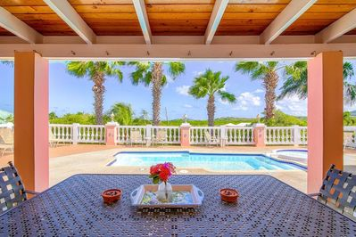 Large dining table on the covered deck overlooking the pool and yard