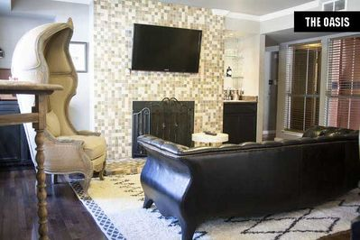 The Oasis Living Room with flat screen television, fireplace, and wet bar.