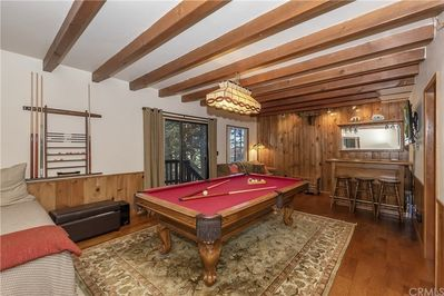 Family/Game room w/pool/ping pong table, TV, bar and bathroom.  Pullout sofa