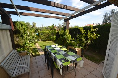 Shaded terrace with table, chairs, sunblind and barbecue - private garden -
