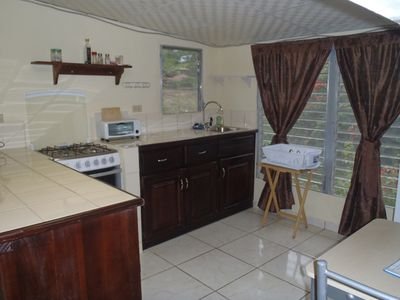 Kitchen with stove/oven, refrigerator, coffee maker, toaster oven.