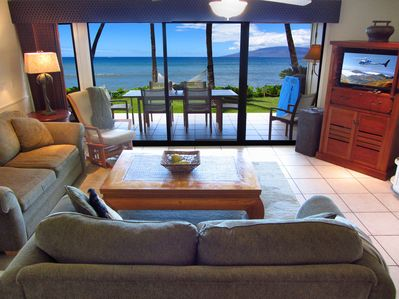 Living Room with couch and queen sleeper looking out at the ocean and Lanaii.