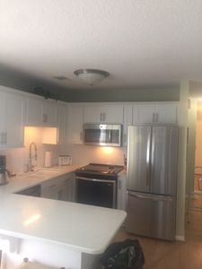 kitchen with 3 counter stools plus large table