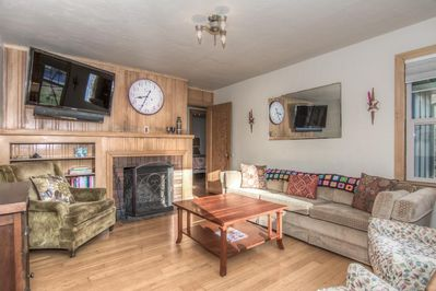 Warm and inviting living room with wood fireplace, original floors, midcentury inspiration!